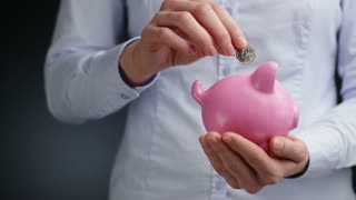 A young businesswoman holds a piggy bank in her hand and puts a 1 Euro coin in it.