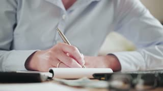 A businesswoman writes down notes on a paper notebook. Closeup static footage.