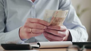 A young businesswoman counts Euro banknotes and takes notes on a paper notebook. Closeup static footage.