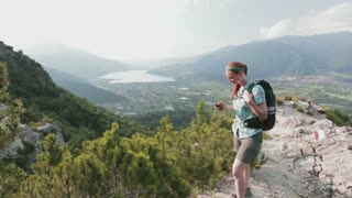 A female hiker navigates a scenic trail overlooking an Alpine lake in Italy.