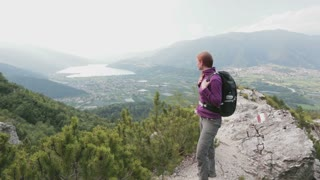 A young woman with a backpack hikes up a scenic Alpine trail in Northern Italy, overlooking lake Lago di Caldonazzo.