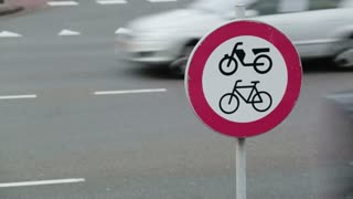 Cars pass on a city street behind a traffic sign indicating a road closed to bicycles and mopeds. Camera panning move.