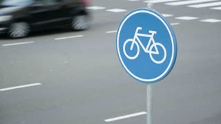 Cars pass on a city street behind a traffic sign indicating a mandatory lane for bicycles.