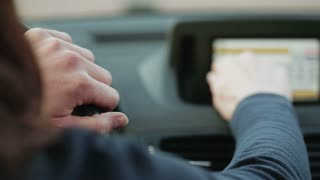 A female car driver enters and address in the satellite navigation of her car and holds the steering wheel.