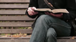 A young woman closes a Bible and begins to pray. Closeup footage in a park by autumn.