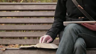 Woman studies the Bible in a park. Closeup footage.