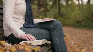 Woman studies the Bible in a park with the help of a tablet.