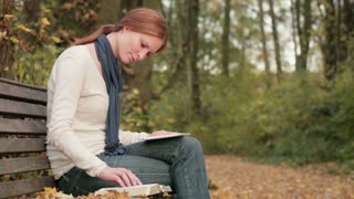 Christian woman studies the Bible with a tablet on a bench in a park by autumn.