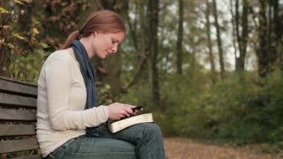 A young woman with a Bible and a mobile phone in a park.