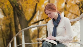 A woman reads the Bible in a park and looks up in thought.