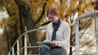Footage of a woman using a touch screen tablet outdoors in a park by autumn.