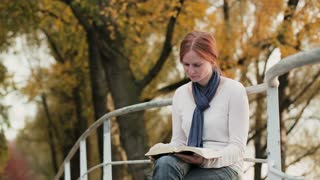 A young woman reads the Bible and prays in a park by autumn.