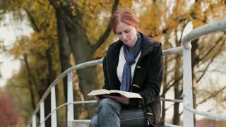 A young woman reads the Bible in a public park by autumn.