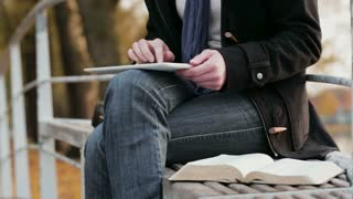 A young woman takes notes on a tablet while reading the Bible in a park by autumn.