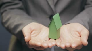 New or energy efficient home concept - a business woman holds a small paper house in her hands.