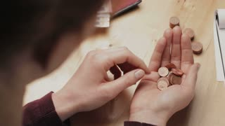 Over the shoulder view of a woman counting Euro coins at a table.