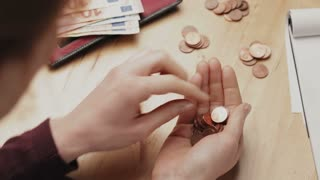 Over the shoulder view of a young woman counting Euro coins at a table at home.