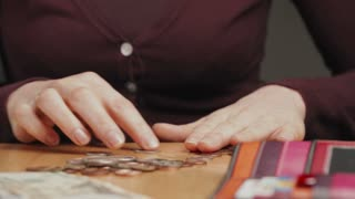 Dolly shot of a housewife counting coins on a table.