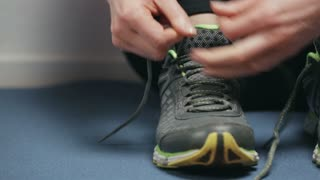 A young active woman tying running shoes. Closeup dolly shot.