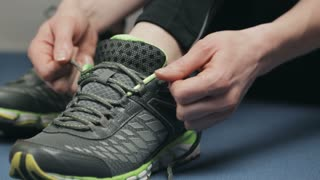A young active woman tying running shoes. Closeup static footage.