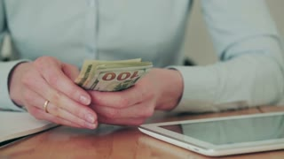 A business woman counts American dollars by hand. Closeup static footage.