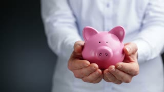 A business woman holds a pink piggy bank in her hands at waist level, copy space on the side.