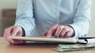 A businesswoman uses a tablet to do online banking or shop via a web store. Closeup footage over a wooden table with US banknotes.