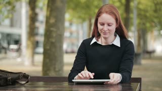 A casual woman sits at a table in a public park and uses a tablet computer. Copy space available.
