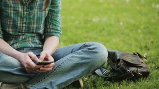 A casual young woman typing an SMS or a text message on a mobile phone while sitting on a grass field in a park. The camera pans from right to left.