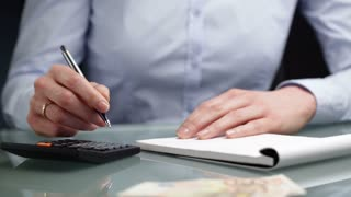 A female accountant or office assistant makes and writes down money calculations on a notebook.