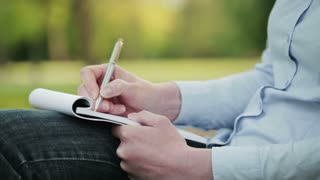 A female college student takes notes on a paper notepad while sitting in a public park. Closeup static footage.