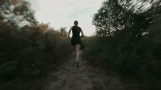 A female cross country runner training on a narrow beach trail by sunset in the summer.