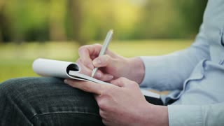 A female student takes notes on a paper notepad while sitting in a public park. Closeup footage, the camera pans from right to left to reveal copy space.