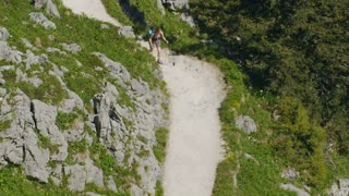 A fit young woman hiking alone on a mountain trail by summer. High angle shot.