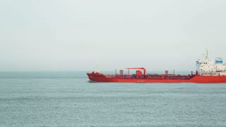 A red chemical cargo ship at sea passes before the camera.