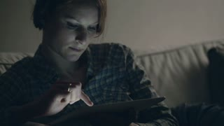 A relaxed young woman uses a tablet computer at home late in the evening or at night under dim lighting. Dolly shot.