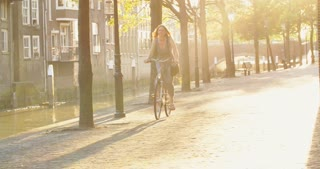 A smiling young woman on a bicycle on a street in an old European town. Shot by sunset.