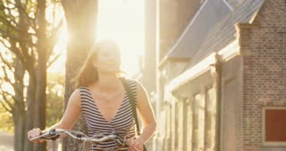 A smiling young woman pushes a bicycle on a street in an old European town. Shot by sunset.