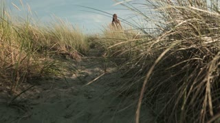 A woman in a summer dress walks toward the camera on beach dunes.