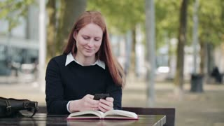A woman sends text messages or SMS on a mobile phone from a city park and then looks up to her side.