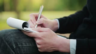 A woman takes notes on a paper notepad while sitting in a public park. Closeup footage, the camera tilts up to reveal copy space.