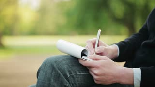 A woman takes notes on a paper notepad while sitting in a public park. Closeup footage, the camera tilts up.