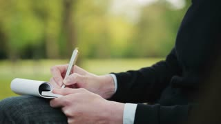 A woman takes notes on a paper notepad while sitting in a public park. Closeup footage with copy space and people passing in the far background.