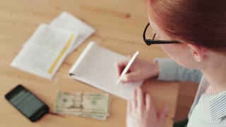 A young businesswoman does finances on a paper notebook over a wooden desk or a table at home or in an office. Top view, static footage.