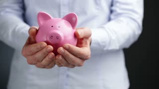 A young businesswoman holds a pink piggy bank at waist level with copy space on the side.