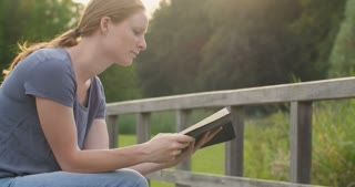 A young Christian woman reading the Bible and praying in a park.