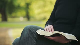 A young Christian woman reads the Bible in a park and flips a page. Closeup frame.