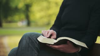 A young Christian woman reads the Bible on a bench in a park and flips a page. Panning move from left to right.
