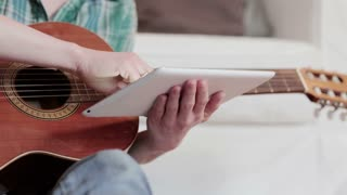A young musician opens notes on a tablet computer and practices the acoustic guitar in her living room before a white couch. Sliding dolly shot.