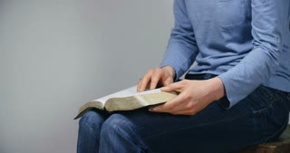 A young woman closes a Bible and prays. Medium tilt shot.